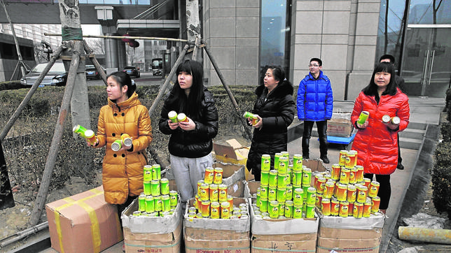 Employees of Chinese multimillionaire Chen Guangbiao's company give away cans of fresh air to pedestrians near a street on a hazy day in central Beijing -03NT2594.jpg-