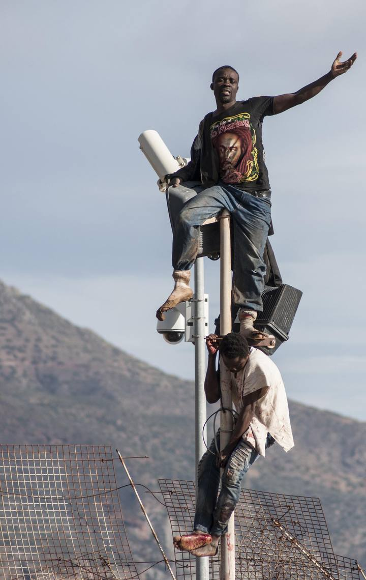 African migrants sit on top of a border fence between Morocco and Melilla