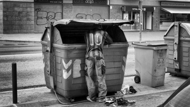 Un hombre busca comida en un contenedor de basura; es España